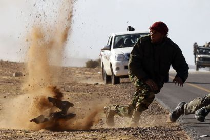 Rebel fighters jump away from shrapnel during heavy shelling by forces loyal to Libyan leader Muammar Gaddafi near Bin Jawad, March 6, 2011. Rebels in east Libya regrouped on Sunday and advanced on Bin Jawad after forces loyal to Muammar Gaddafi ambushed rebel fighters and ejected them from the town earlier in the day.  REUTERS/Goran Tomasevic (LIBYA - Tags: POLITICS CIVIL UNREST)